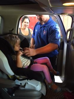 Technician buckles child's seat belt.