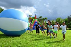 children running alongside giant inflatable ball