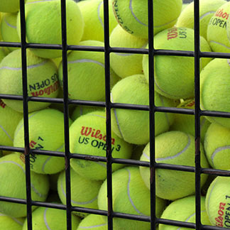 a lot of tennis balls in a basket