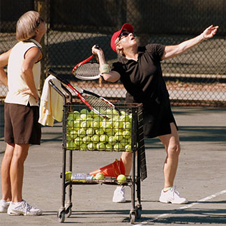 pro teaching person how to serve a tennis ball