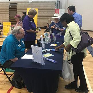 seniors at a health fair visiting a booth to get information