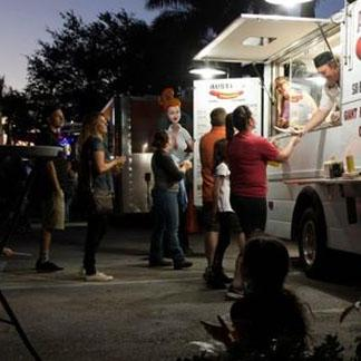 group of people lined up to buy food at a food truck
