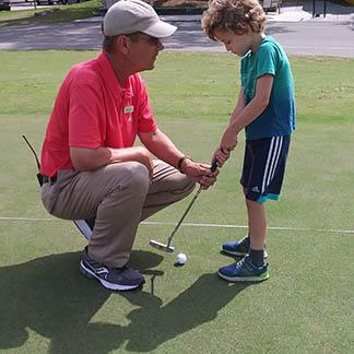 golf pro with little boy and golf club
