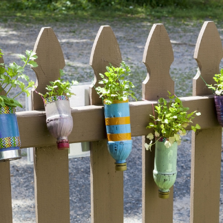 Decorated bottle planters on a fence.