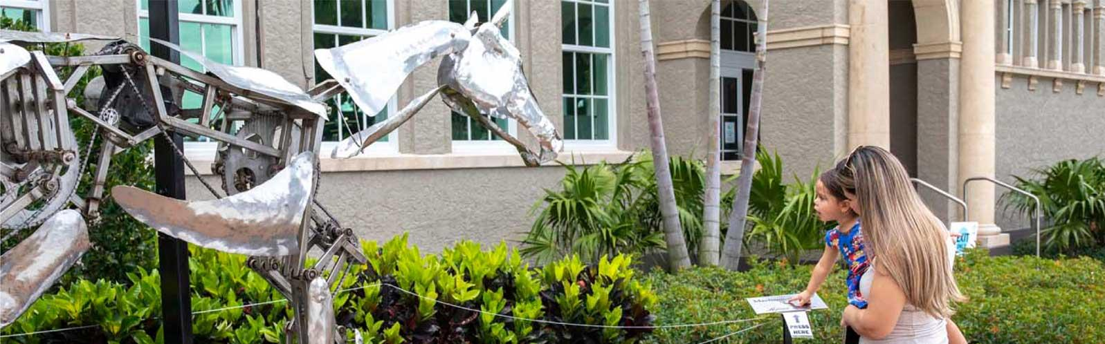 Two people next to kinetic art, horse sculpture.
