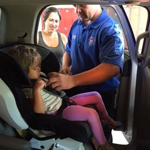 firefighter installing a car seat with a mom watching