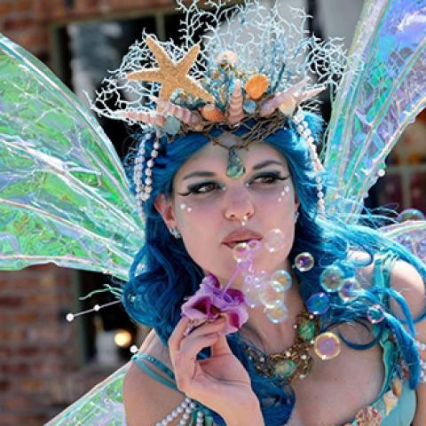 girl in mermaid costume blowing bubbles